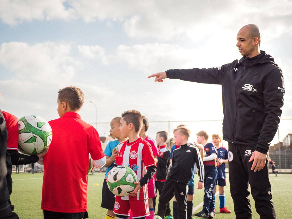 Reguillo Vandepitte, van Skills & Control, geeft jonge voetballers uitleg tijdens een training op het voetbalveld.
