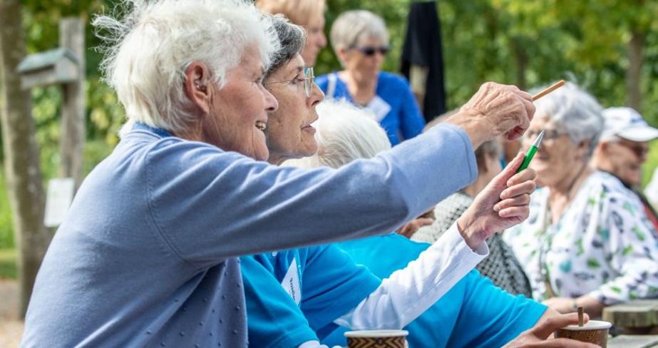 Ouderen genieten buiten van een kopje koffie en nemen deel aan een activiteit tijdens de Walcherse Ontmoetingsdagen. Foto door Mieke Wijnen Fotografie