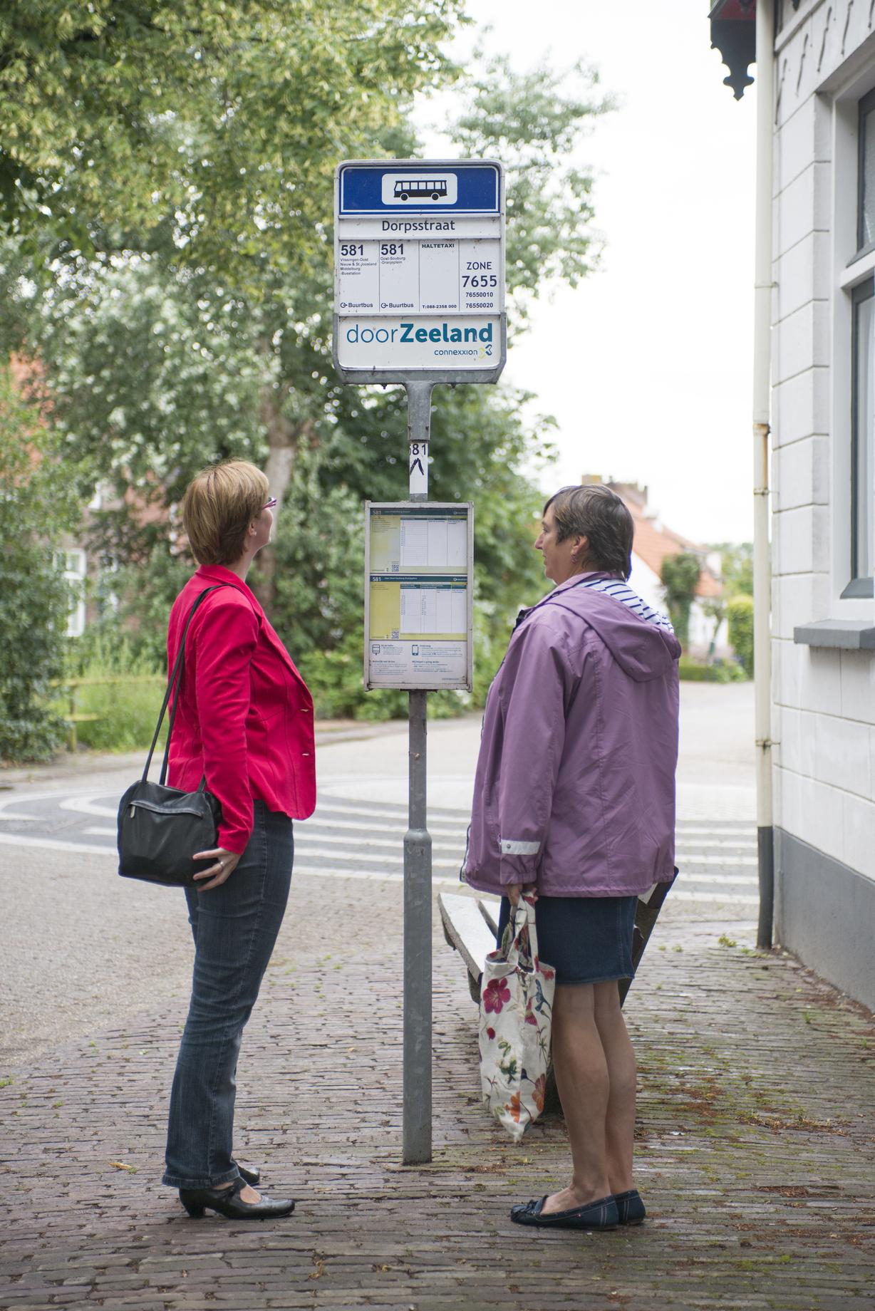 Twee reizigers bij de bushalte in Zeeland