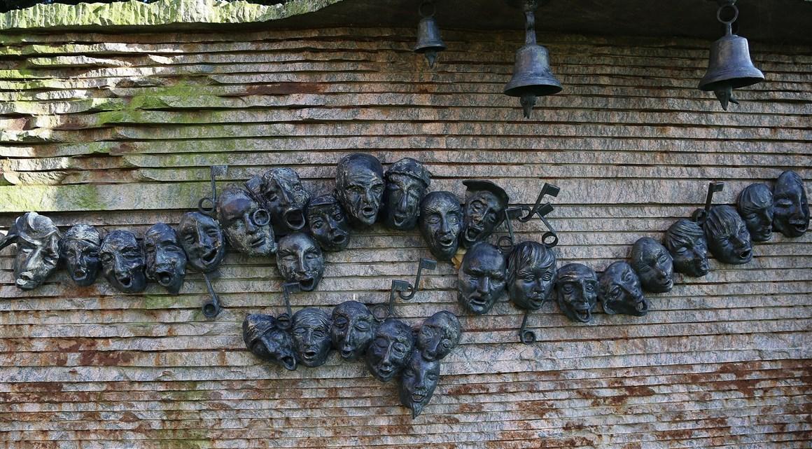 """Bij de St. Bavokerk in Aardenburg hangt deze verzameling van """"bonte koppen"""" die samen zingen. Iedere """"kop"""" heeft een eigen uitdrukking."""