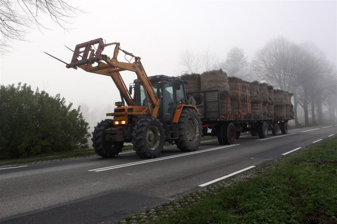 Landbouwvoertuig op de weg in de mist