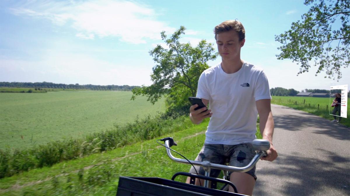 Jongen op fiets met smartphone in de hand